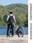 Small photo of standing female bicyclist wearing helmet and backpack admires beautiful early autumn landscape in sunny morning during halt at sand beach, Riviere-Rouge, Corridor Aerobique, Quebec, Canada
