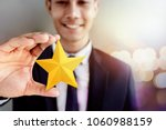 Small photo of Success in Business or Personal Talent Concept. Happy Businessman in black suit Smiling and Showing a Golden Star in Hand