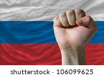 complete national flag of russia covers whole frame, waved, crunched and very natural looking. In front plan is clenched fist symbolizing determination - stock photo