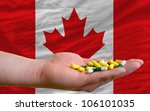 man holding capsules in front of complete wavy national flag of canada symbolizing health, medicine, cure, vitamins and healthy life - stock photo