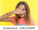 Small photo of Portrait of teenage girl peeps through fingers. Yellow studio background