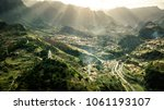 Aerial view on small city Sao Vicente - red rooftops, chapel on the hill, huge mountains on background and beautiful soft sunlight, Madeira island, Portugal.