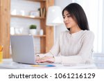 Small photo of Bad proposition. Beautiful charming female freelancer using laptop and posing at table