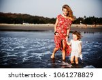 mom and daughter on the beach   Shutterstock . vector #1061278829