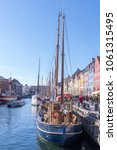 Small photo of COPENHAGEN, APRIL 2, 2018: Tourists slowly amble along Nyhavn in Denmark admiring the colourful buildings and ships