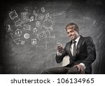 Smiling young businessman using a mobile phone with symbols beside him - stock photo