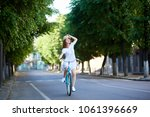 pensive girl rides on the road... | Shutterstock . vector #1061396669