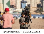 Small photo of Benidorm, Spain, 28/03/2018: Camcorder on the tripod. The operator and the announcer are preparing the airtime on the Levante beach.