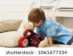 child in bedroom kiss toy in... | Shutterstock . vector #1061677334