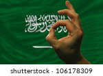 man showing excellence or ok gesture in front of complete wavy saudi arabia national flag symbolizing best quality, positivity and success - stock photo