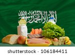 complete national flag of saudi arabia covers whole frame, waved, crunched and very natural looking. In front plan are fundamental food ingredients for consumers, symbolizing consumerism - stock photo
