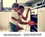 Black Kid Helping Mom Baking...