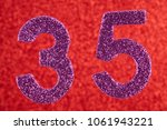 Small photo of Number thirty-five purple color over a red background. Anniversary. Horizontal