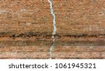 old cracked red brick wall... | Shutterstock . vector #1061945321