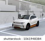 white electric suv charging at... | Shutterstock . vector #1061948384