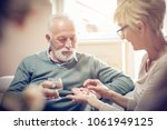 senior woman giving her husband ...   Shutterstock . vector #1061949125