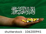 man holding capsules in front of complete wavy national flag of saudi arabia symbolizing health, medicine, cure, vitamins and healthy life - stock photo