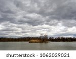 Islet on pond under cloudy sky