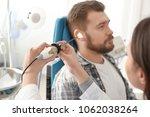 otolaryngologist examining man...   Shutterstock . vector #1062038264