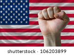 complete american national flag covers whole frame, waved, crunched and very natural looking. In front plan is clenched fist symbolizing determination - stock photo