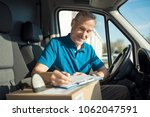 happy delivery man with... | Shutterstock . vector #1062047591