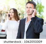 Small photo of Indifferent girl and guy speaking on phones while walking together