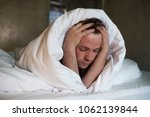 depressed man lying in his bed... | Shutterstock . vector #1062139844