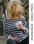 woman holding a cup at garden. | Shutterstock . vector #1062179621