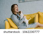 Stock photo attractive pregnant woman laughing and playing with jack russell terrier in living room 1062230777