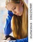 Small photo of People and solitude concept. Alone sad troubled young woman long hair teen girl sitting on window sill lost in thought