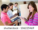 Small photo of Woman with tablet computer reading an e-book and friends carrying heavy books