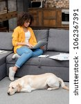 Stock photo beautiful young woman working at home while her dog lying on floor 1062367391