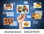 Woman hand uses touch screen interface with food - stock photo
