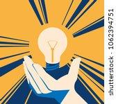 lightbulb in hand with glow.... | Shutterstock .eps vector #1062394751