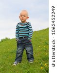 Small photo of little boy in jeans and raglan stands outside in the spring, hands in pockets