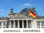 German flag waving at Bundestag building in Berlin Germany front facade view in a sunny day with blue sky.