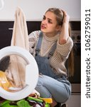 Small photo of Portrait of american housewife feeling miserable taking dirty clothes out washer