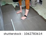 worker laying floor tiles | Shutterstock . vector #1062783614