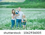 young family in a field of... | Shutterstock . vector #1062936005