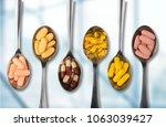 supplements on metal teaspoons | Shutterstock . vector #1063039427