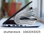 newspapers and laptop. pile of... | Shutterstock . vector #1063243325