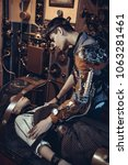 Small photo of A scientist, a mechanic, includes a control lever to revive an artificial robot girl on a desk in his steampunk lab. Steampunk story.