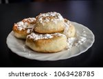 Small photo of White Plate with Donuts and Powdered Sugar ono black background