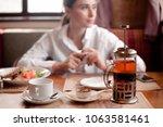 girl having breakfast at a... | Shutterstock . vector #1063581461
