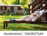child girl relaxing on sunbed...   Shutterstock . vector #1063827164