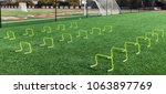 Small photo of 12 inch banana hurdles set up on a green turf field for speed training at track and field practice.