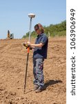 Small photo of Woubrugge, Netherlands - June 4, 2013: technician reading height measurements with a GPS operated device on a reenforced dike; in the backgroud a crane is compacting the crest of the dike