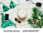 Small photo of Bikini suit, hat, sunglasses, film camera, smartphone, sea star, green plam leaves arranged on wooden baclground. Summer holidays vacation concept.