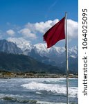 Small photo of Red danger warning flag. Location: Marinella, Massa Carrara, Italy. Apuan Alps with snow in the background. NOTE differential focus, focused on flag.