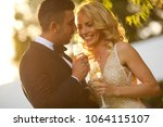 newlyweds drinking champagne on ... | Shutterstock . vector #1064115107